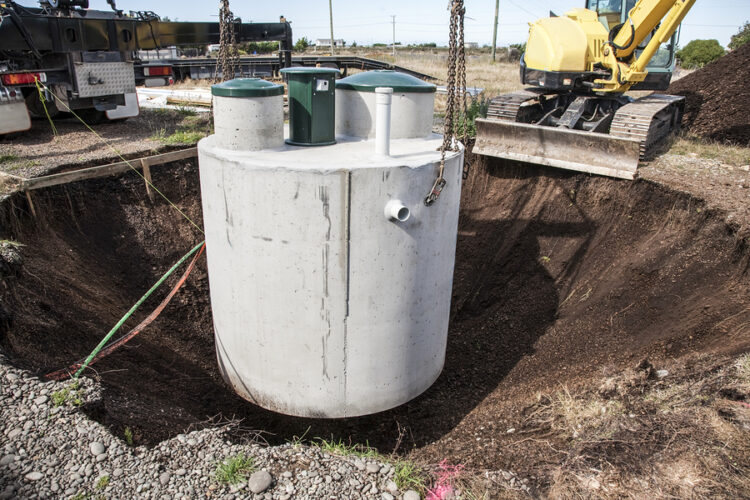 environmentally friendly septic tank being lowered into ground
