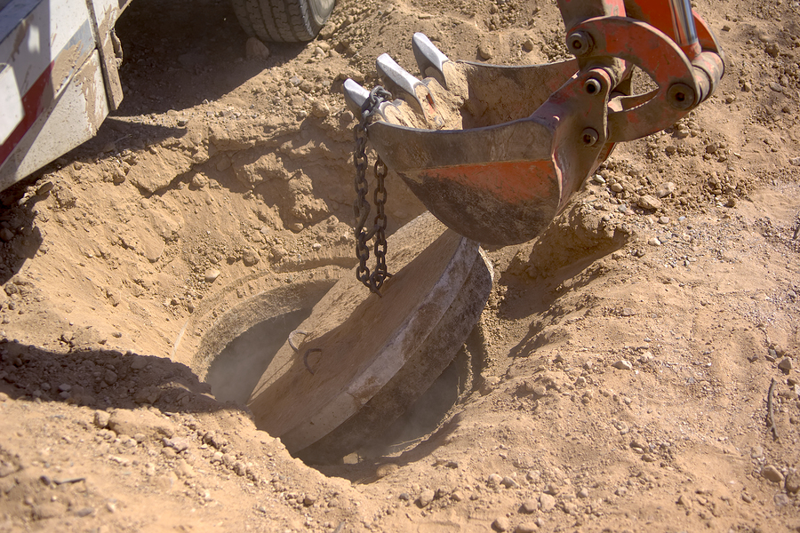 the concrete lid of a septic tank being popped open